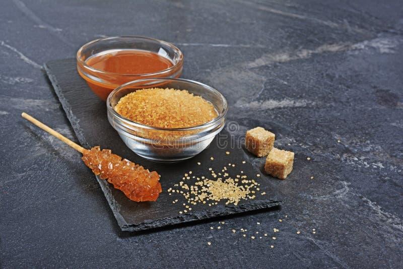 Salsa dolce casalinga del caramello in ciotola di vetro e zucchero di canna marrone con il bastone a cristallo dello zucchero immagine stock libera da diritti