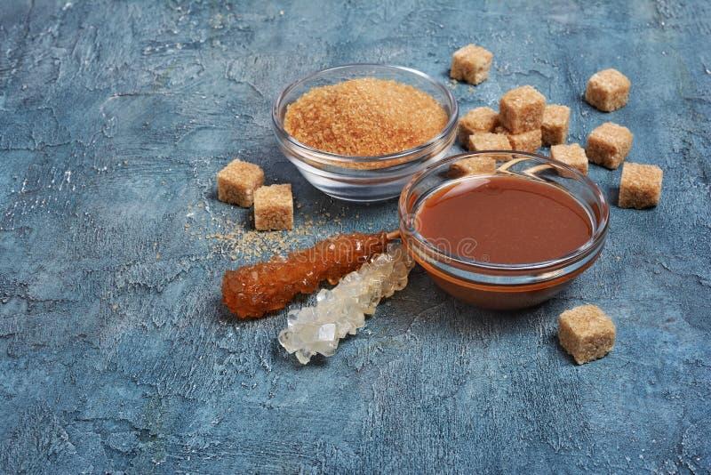 Salsa dolce casalinga del caramello in ciotola di vetro e zucchero di canna marrone con il bastone a cristallo dello zucchero fotografia stock