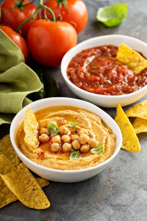 Salsa fait maison de houmous et de tomate dans des cuvettes blanches avec des puces photographie stock libre de droits