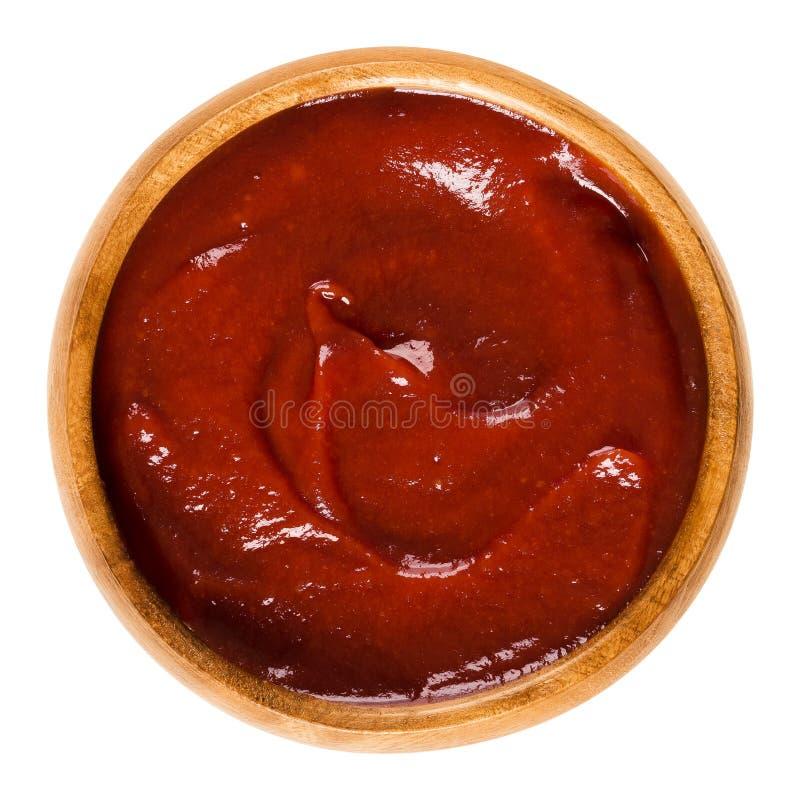 Salsa ketchup in ciotola di legno sopra bianco fotografie stock