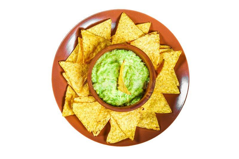 Salsa messicana tradizionale del guacamole fatta dai nacho dei chip della calce e dell'avocado su un fondo bianco Il guacamole ed fotografia stock libera da diritti
