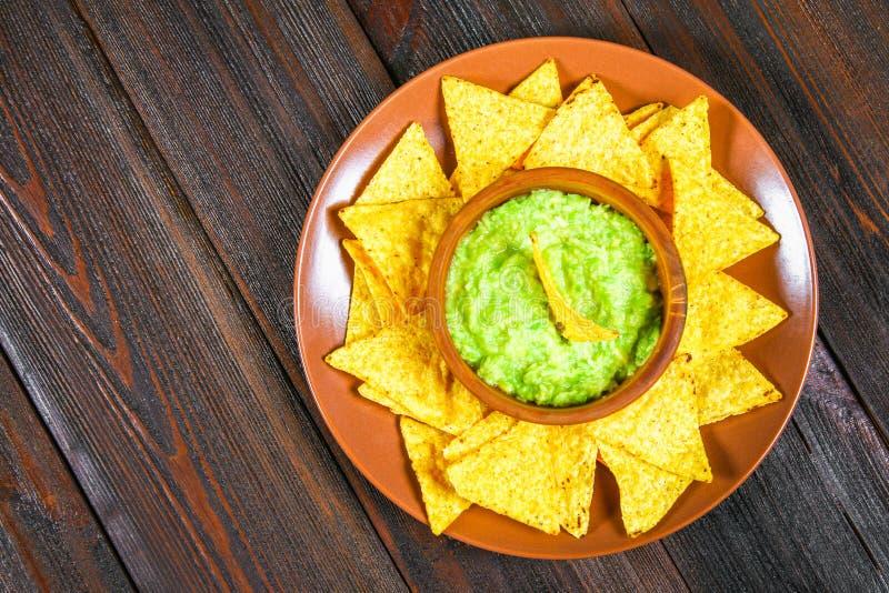 Salsa messicana tradizionale del guacamole fatta dai nacho dei chip della calce e dell'avocado su una tavola di legno marrone Vis fotografia stock
