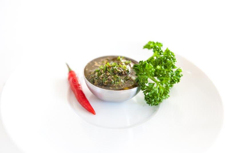 Salsa ou sauce vert argentin fait maison cru de Chimichurri d'isolement sur un fond blanc photos libres de droits