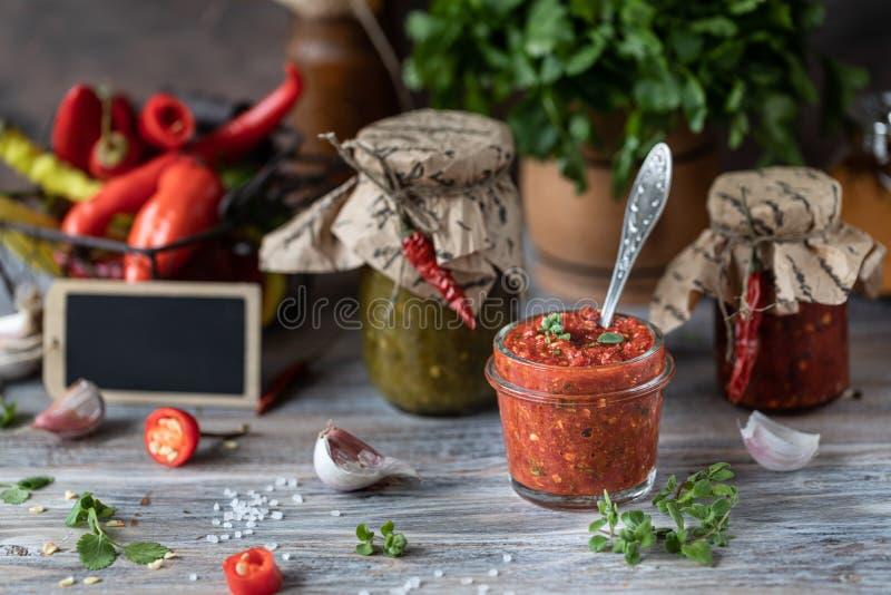 Salsa piccante pronta in barattoli di vetro dei peperoncini rossi e verdi fotografie stock