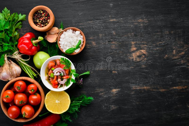 Salsa sauce and ingredients. Latin American Mexican Traditional Sauce. Top view. On a black background. Free space for text royalty free stock photo