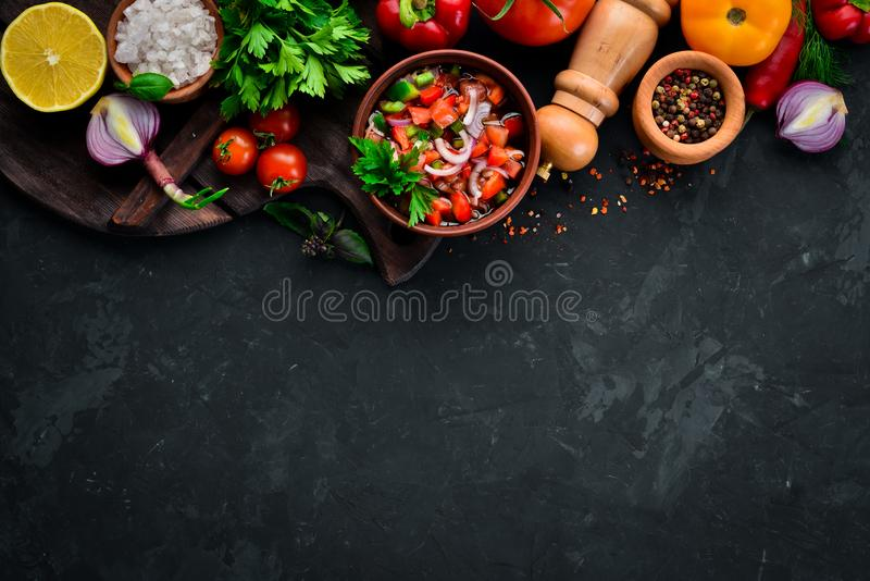 Salsa sauce and ingredients. Latin American Mexican Traditional Sauce. Top view. On a black background. Free space for text royalty free stock image