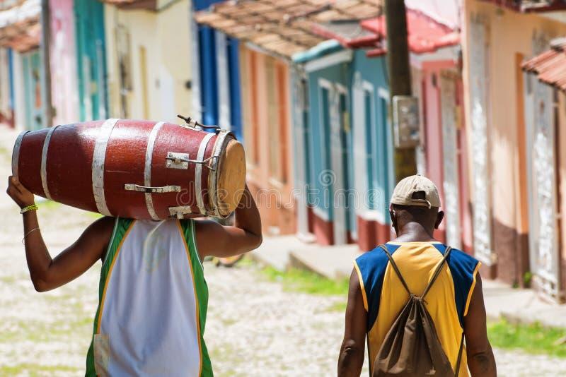 Salsamusiker som bär en conga, medan gå i gatorna av Trinidad Cuba med en vän arkivfoton