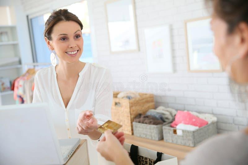 Salseswoman in de kledingswinkel die uit de aankoop van haar klant munt slaan stock fotografie