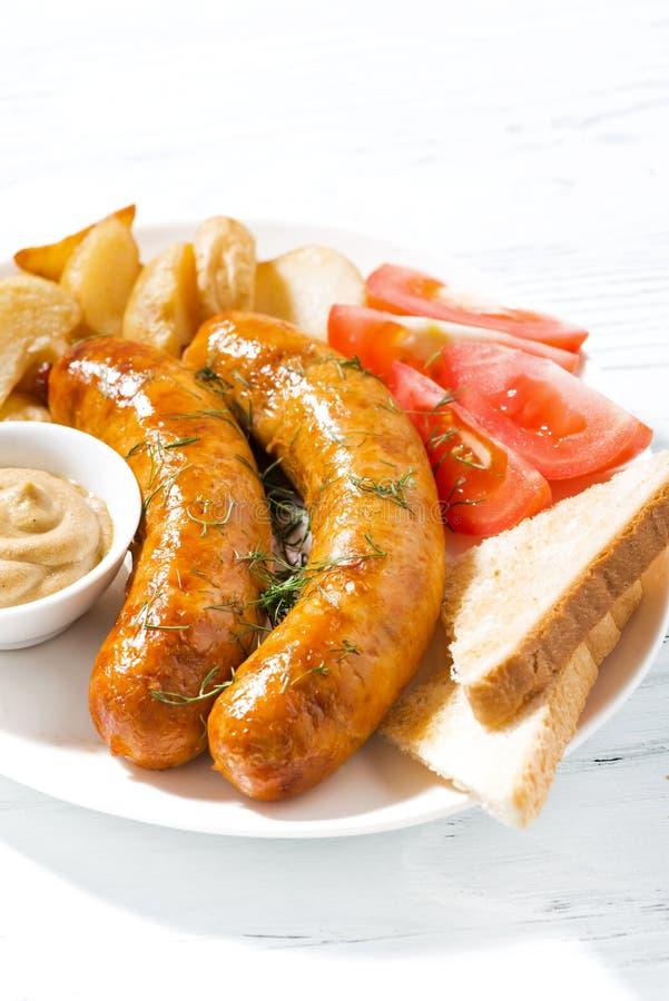 Salsicce di maiale fritte con le patate e la senape, primo piano verticale immagini stock libere da diritti