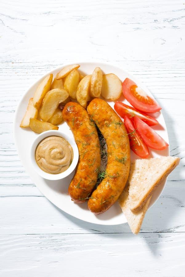 Salsicce di maiale fritte con le patate e la senape, vista superiore fotografia stock libera da diritti