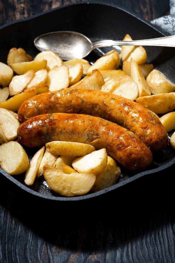 Salsicce di maiale fritte con le patate in padella, primo piano fotografia stock