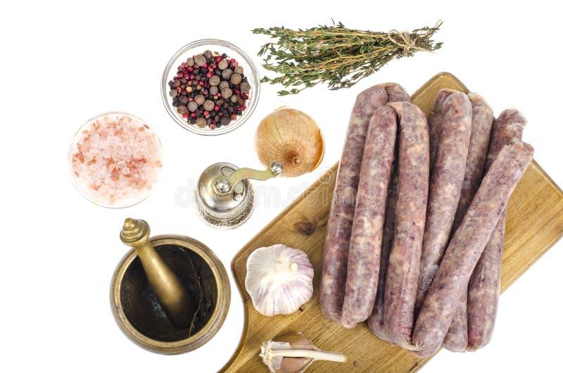 Salsiccia casalinga cruda in intelaiatura naturale, spezie, erbe per cucinare fotografia stock