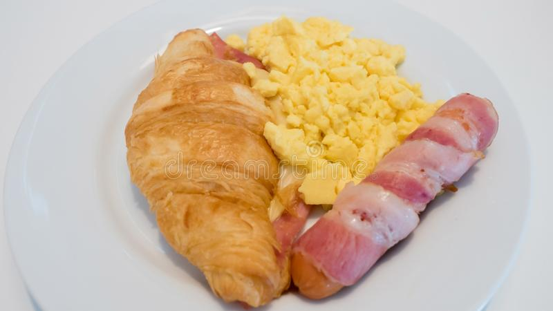 Salsiccia del formaggio del croissant, bacon, uova rimescolate sul Cl bianco del piatto immagine stock