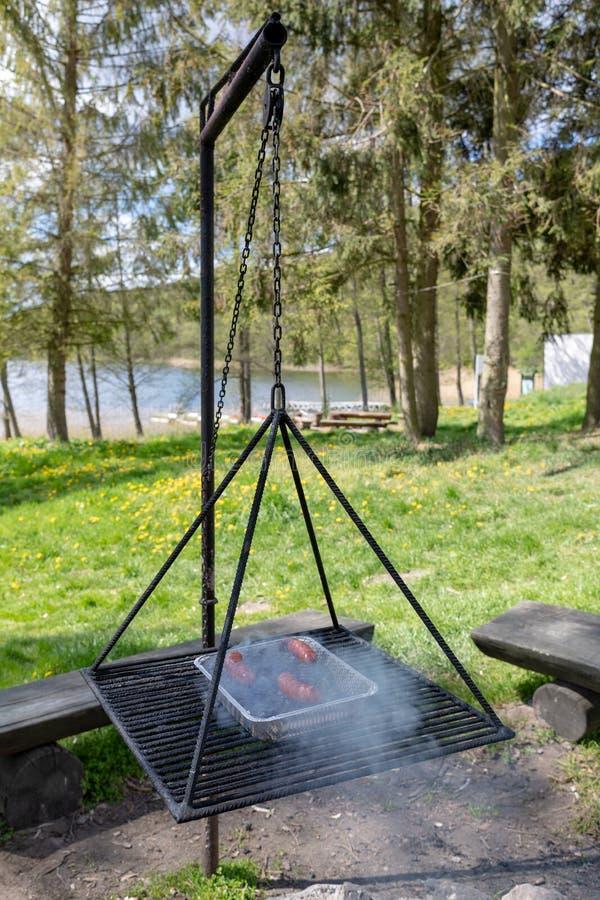 Salsiccia dell'arrosto sulla griglia Preparazione del pasto su un campeggio fotografia stock