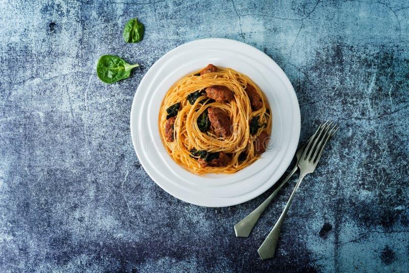 Salsiccia di pomodoro Spinach Pasta di pasta in una piastra bianca immagini stock