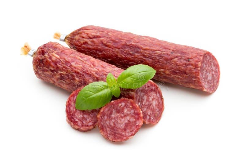 Salsiccia, foglie del basilico fumate salame e granelli di pepe isolati sopra fotografia stock