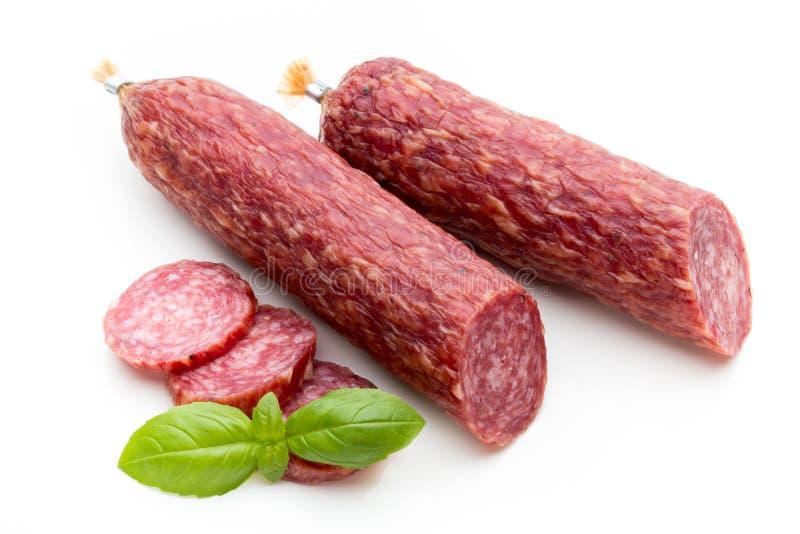 Salsiccia, foglie del basilico fumate salame e granelli di pepe isolati sopra fotografie stock libere da diritti