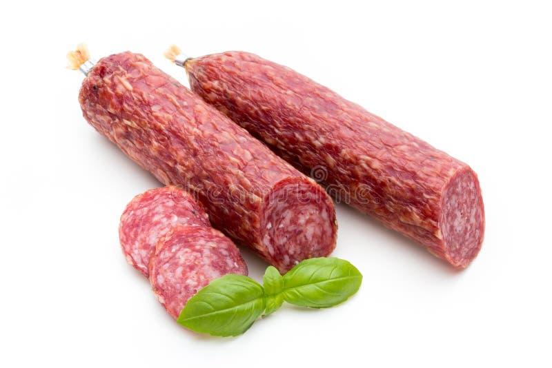 Salsiccia, foglie del basilico fumate salame e granelli di pepe isolati sopra fotografia stock libera da diritti
