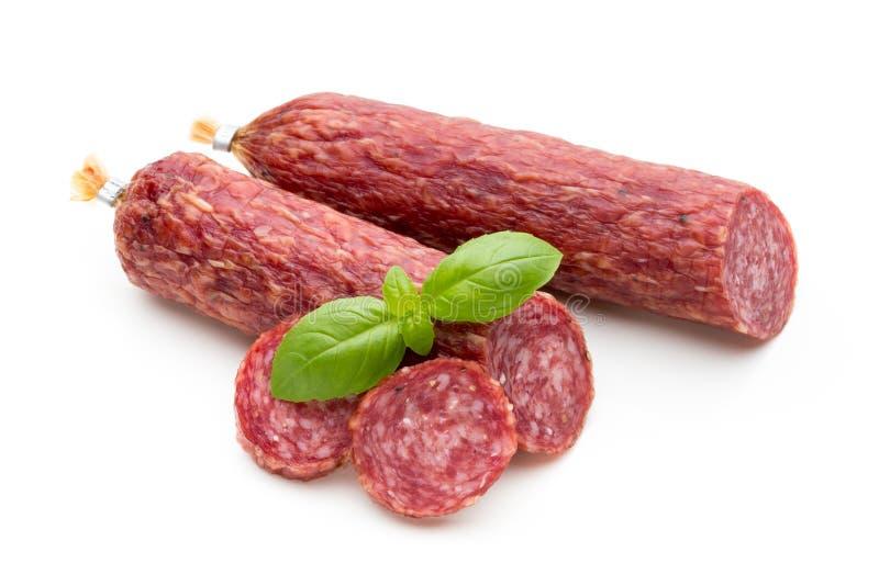 Salsiccia, foglie del basilico fumate salame e granelli di pepe isolati sopra immagine stock libera da diritti