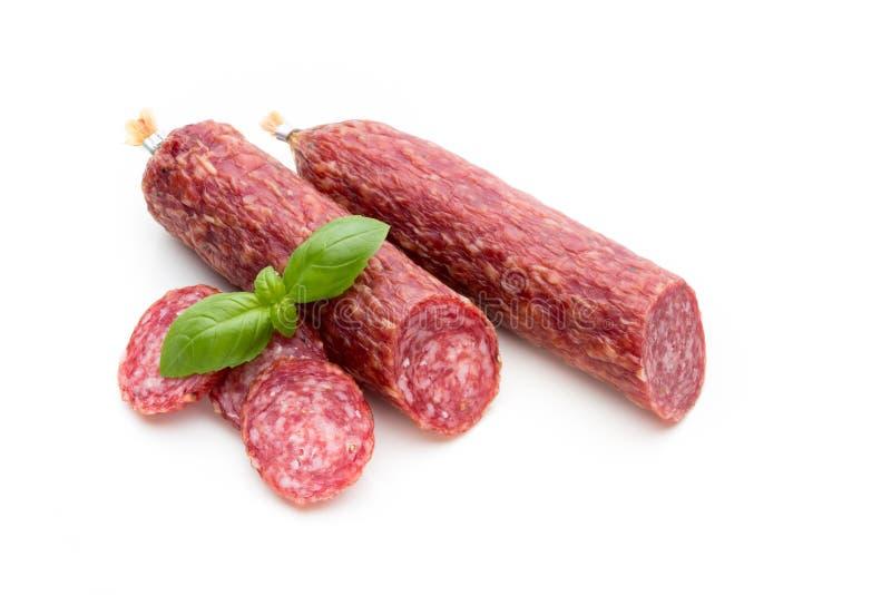 Salsiccia, foglie del basilico fumate salame e granelli di pepe isolati su fondo bianco immagine stock libera da diritti