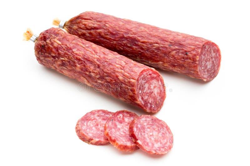 Salsiccia, foglie del basilico fumate salame e granelli di pepe isolati su fondo bianco fotografia stock libera da diritti