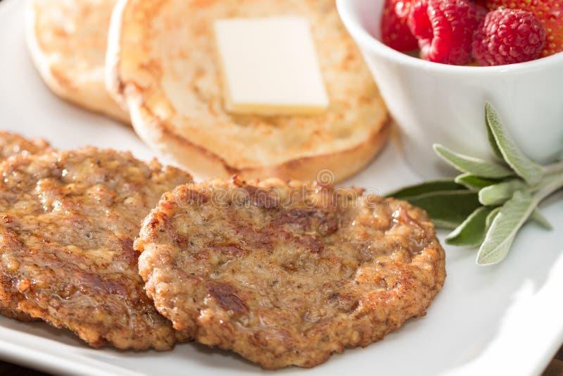 Salsiccia Patty Breakfast con il muffin inglese e la frutta fresca fotografie stock libere da diritti