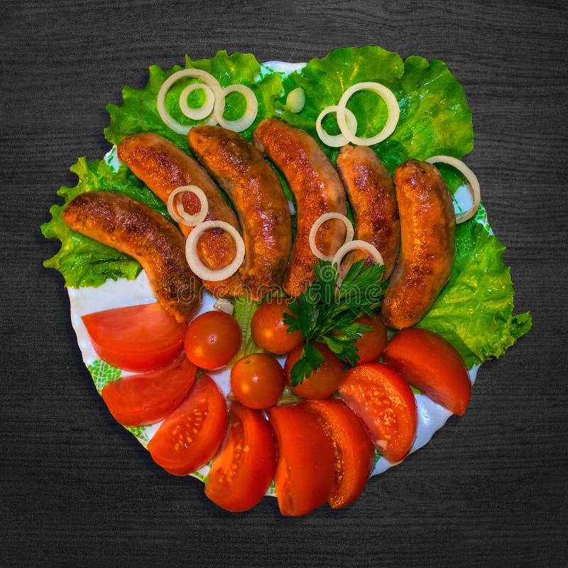 Salsiccia sulla griglia con prezzemolo, i pomodori e le cipolle immagini stock libere da diritti