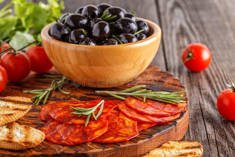 Salsiccia tradizionale spagnola del chorizo con le erbe fresche, olive immagini stock libere da diritti