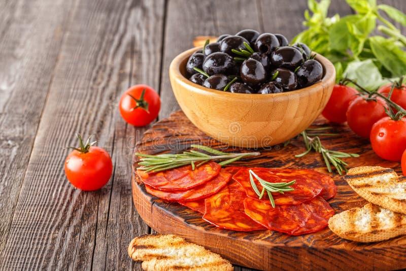 Salsiccia tradizionale spagnola del chorizo con le erbe fresche, olive fotografia stock libera da diritti