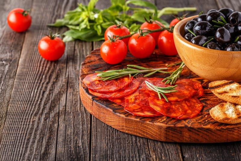 Salsiccia tradizionale spagnola del chorizo con le erbe fresche, olive immagine stock