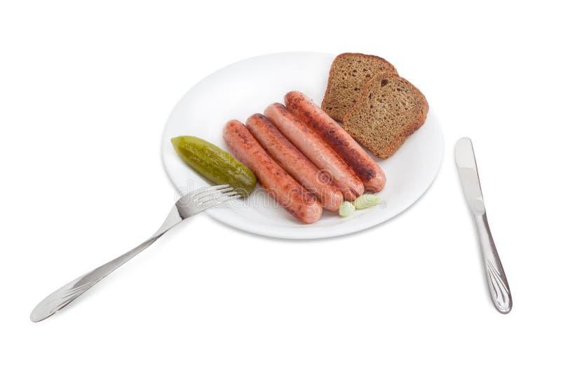 Salsiccie arrostite, cetriolo marinato ed aglio, pane sui Di bianchi fotografia stock libera da diritti
