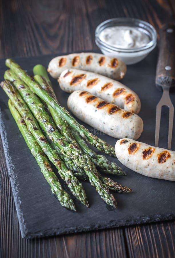 Salsiccie arrostite con asparago e la salsa di aglio cremosa fotografia stock