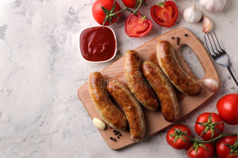 Salsiccie arrostite deliziose su un bordo con salsa e le spezie rosse su un fondo leggero B-B-Q Vista superiore immagini stock