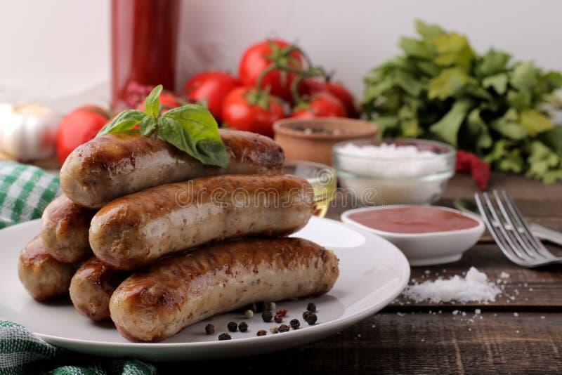 Salsiccie arrostite deliziose su un piatto con salsa e le spezie rosse su un fondo di legno marrone B-B-Q immagine stock libera da diritti