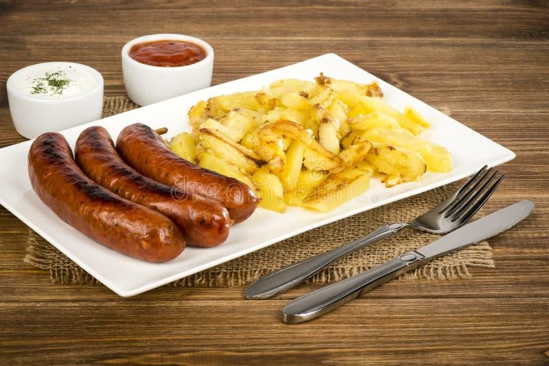 Salsiccie arrostite e patate fritte sul piatto bianco sulla superficie di legno rustica immagine stock