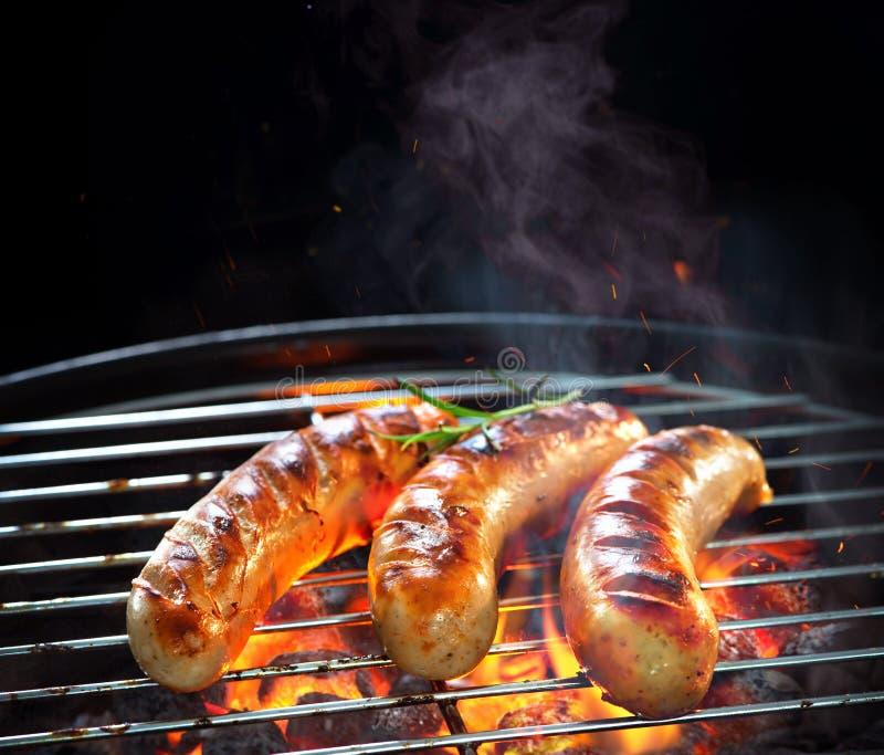 Salsiccie arrostite sulla griglia con fumo e la fiamma fotografie stock