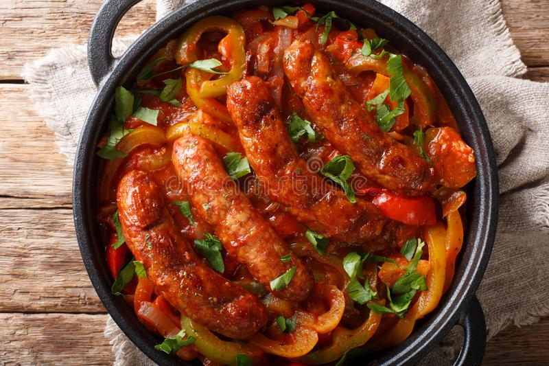 Salsiccie arrostite tradizionali con i peperoni multicolori, le cipolle ed il primo piano dei pomodori in una pentola vista super immagini stock libere da diritti