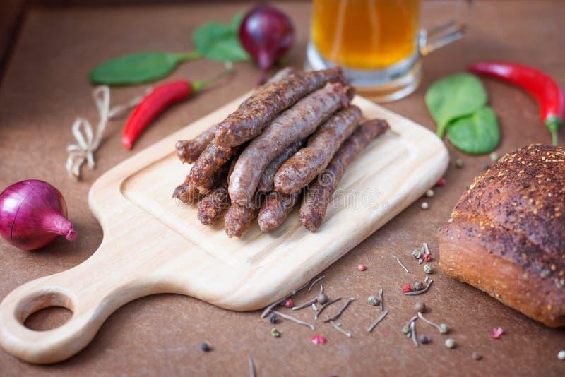Salsiccie arrostite, verdure, spezie e birra del manzo sul plywoo illustrazione di stock