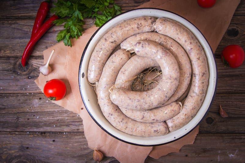 Salsiccie bianche fresche crude su un piatto con le verdure Weisswurst in un mucchio La salsiccia bianca tradizionale di Monaco d fotografie stock libere da diritti