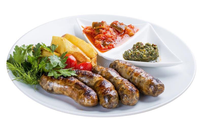 Salsiccie casalinghe con le patate e la salsa Su un piatto bianco fotografia stock libera da diritti