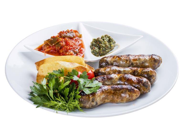 Salsiccie casalinghe con le patate e la salsa Su un piatto bianco fotografia stock