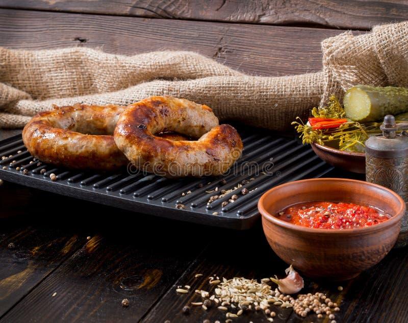 Salsiccie casalinghe piccanti carne di maiale e salsiccie del manzo, su un fondo di legno, con salsa, le spezie ed il cetriolo ma fotografia stock
