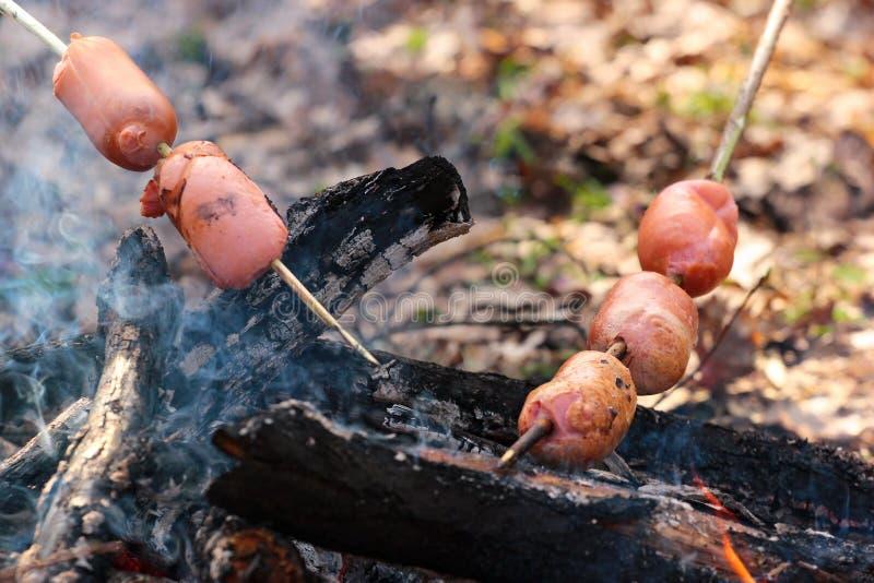 Salsiccie che sono cotte alla griglia su un falò fotografie stock