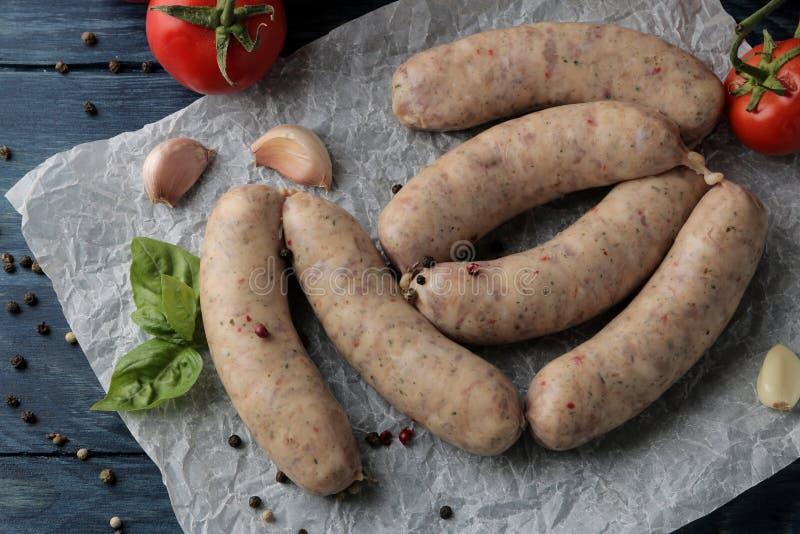 Salsiccie crude con gli ingredienti per la cottura i pomodori, aglio, burro e del basilico su una tavola di legno blu Vista da so fotografia stock libera da diritti