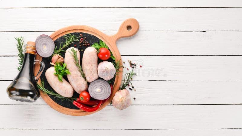 Salsiccie crude con le spezie e le erbe barbecue Su un fondo di legno bianco fotografia stock