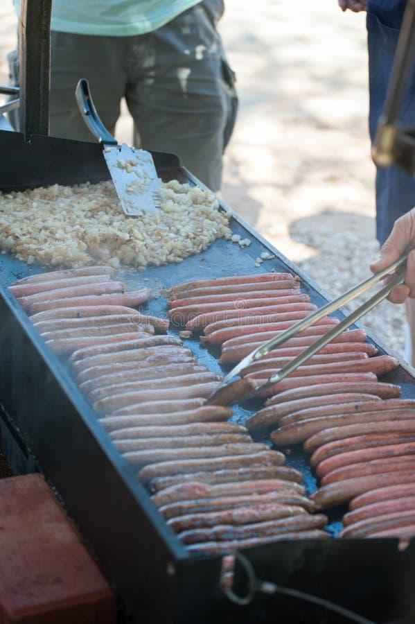 Salsiccie e cipolle che cucinano sulla griglia fotografie stock
