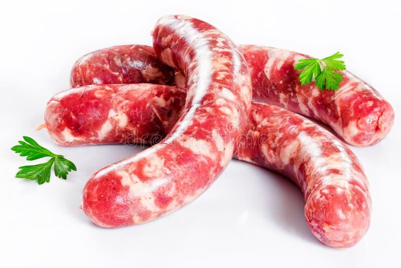 Salsiccie fresche della carne cruda su fondo bianco fotografia stock