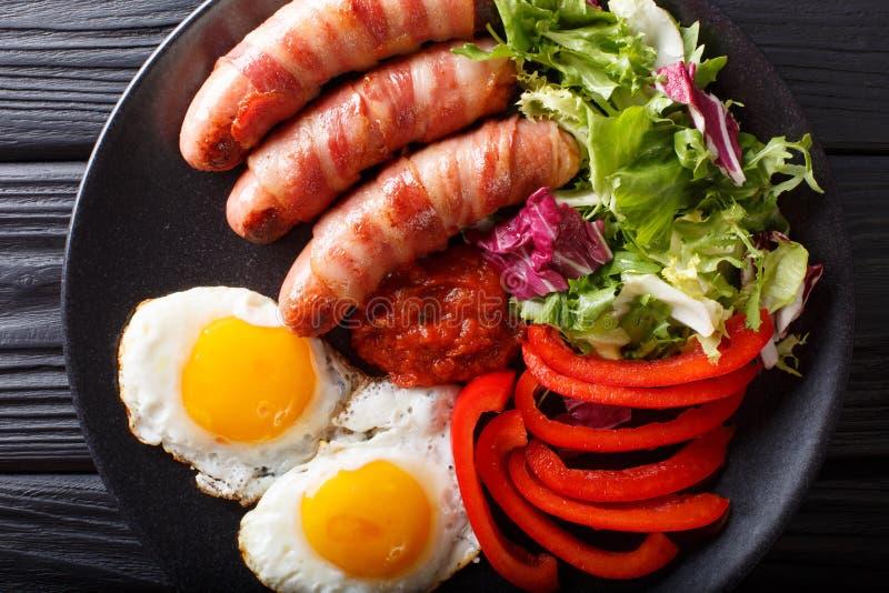 Salsiccie fritte avvolte in bacon, uova e primo piano fresco dell'insalata fotografia stock
