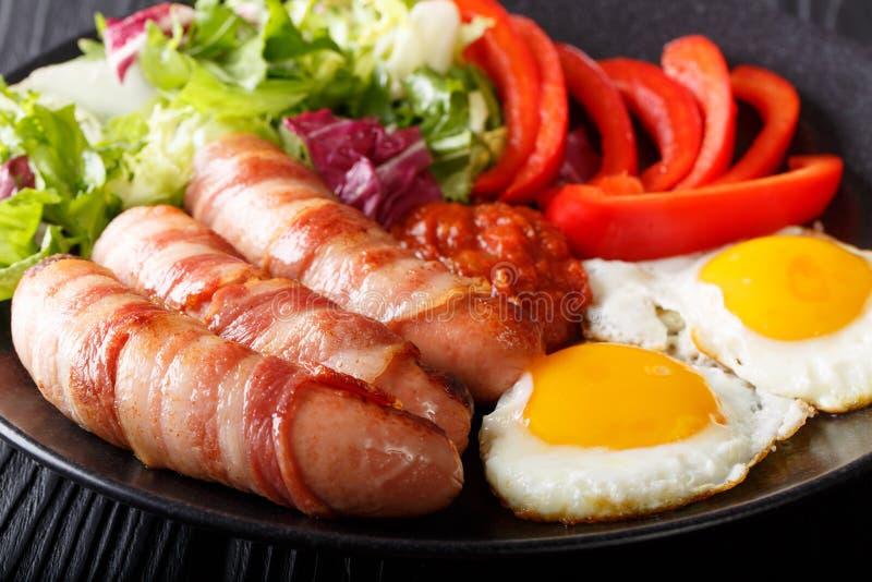 Salsiccie fritte casalinghe avvolte in bacon, in uova, in salsa ed in fresco immagine stock