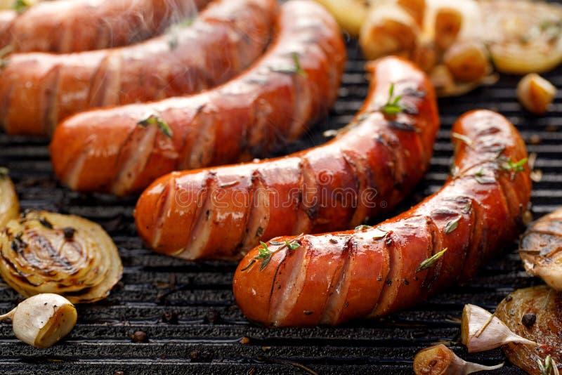 Salsiccie grigliate con l'aggiunta delle erbe e delle verdure sul piatto della griglia, all'aperto, primo piano immagini stock libere da diritti